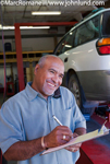 Picture of a Hispanic mechanic Smiling and writing on a clipboard and  working in an auto repair shop
